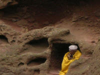 Monk praying in an old grave hollowed from the rock.