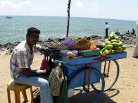 Seller at the beach with various salads