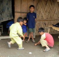 Boys playing a game where coins must be thrown into a small depression in the ground.