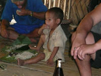 Young boy eating the main meal of rice (Jay)