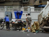 Garbage is brought by collectors using bicycles to the big garbage truck