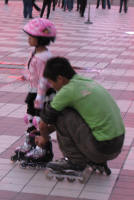 Seen in the evening. Children being taught to roller blade