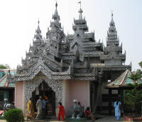 Buddhist Temple flanked by plaster elephants and candle pavilions
