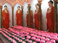 Bodhisattvas with candles purchased by devotees